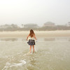 Young girl having fun in ocean waves on a foggy morning,