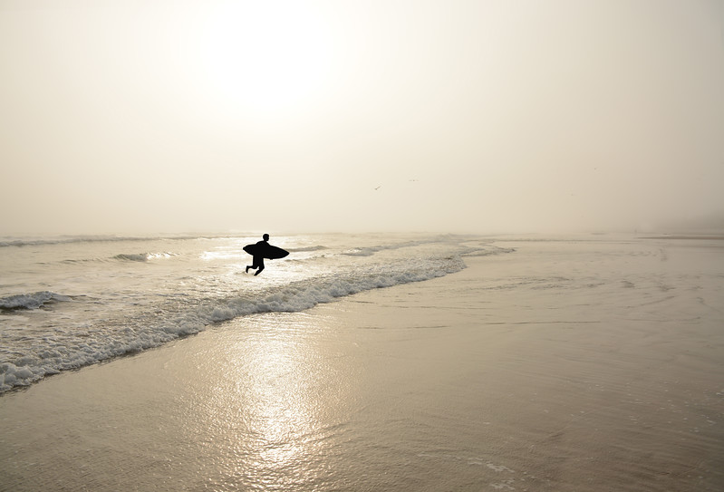 Man  running with surfboard on the beautiful foggy beach.