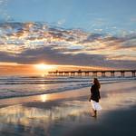 Woman enjoying  on the beautiful beach at sunrise.
