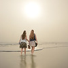 Girls walking on beautiful foggy beach at sunrise.
