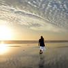 Woman walking on the beach at sunrise.
