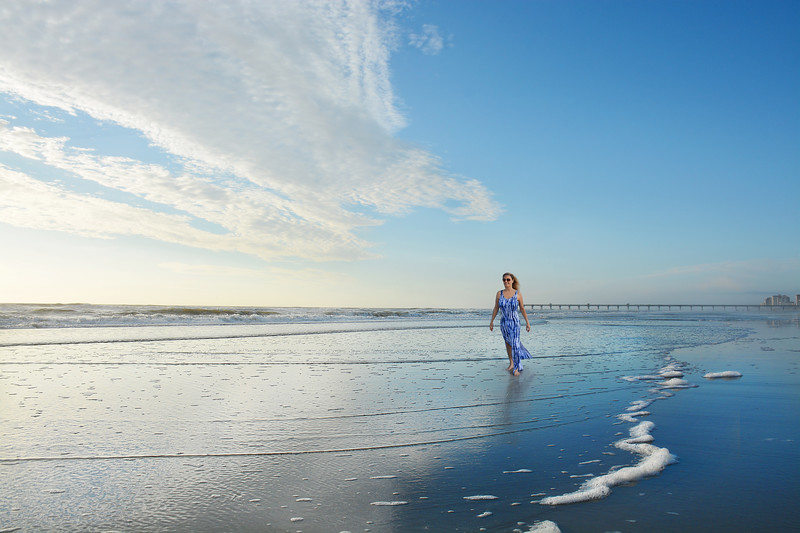 Smiling woman walking  on the beach at sunrise
