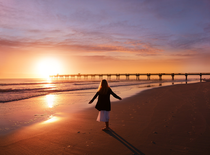 Woman enjoying time on the beautiful beach at sunrise.