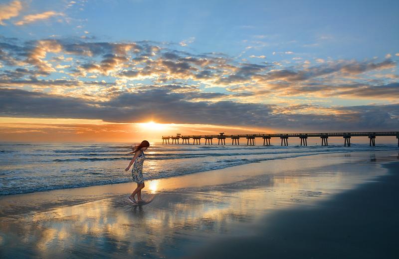 Happy girl walking on the beautiful beach at sunrise.