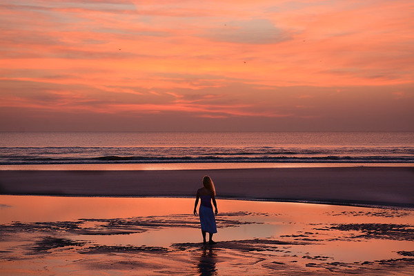 Woman enjoying time on the beach at sunrise.
