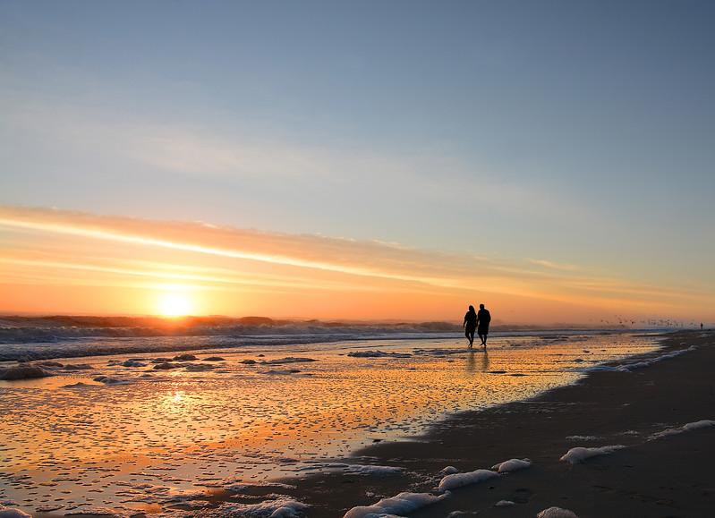 Couple walking on beach at sunrise,.