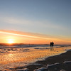 Couple walking on beach at sunrise,.