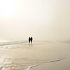 Couple holding hands walking on beautiful foggy beach at sunrise.