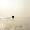 Couple holding hands walking on beautiful foggy beach at sunrise.