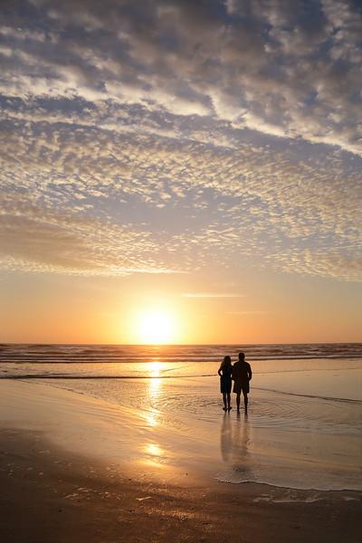 Couple enjoying time on the beach at sunrise.