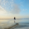 Woman walking and enjoying time on the beach at sunrise