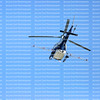 Looking up at a helicopter with spray gear going overhead.