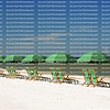 Straight row of green umbrellas with beach chairs facing the waters edge