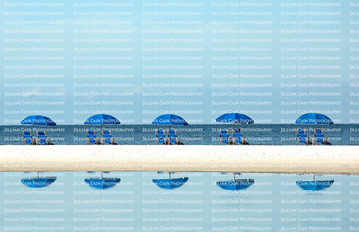 Row of blue umbrellas with matching beach chairs facing the waters edge and reflected in freshwater on the beach