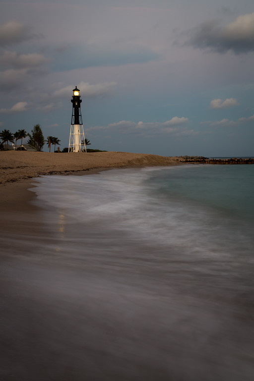 The light of the Hillsboro Inlet lighthouse shines at dusk on a warm late December evening. Pompano Beach, FL<br /> <br /> FL-121226-0024