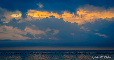 Clouds over old pier at dawn.