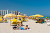 South Beach with apartments and yellow umbrellas on Miami Beach, Florida, USA.