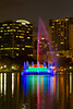 Eola Lake and downtown buildings with colorful water fountain at dusk in Orlando, Florida, USA.