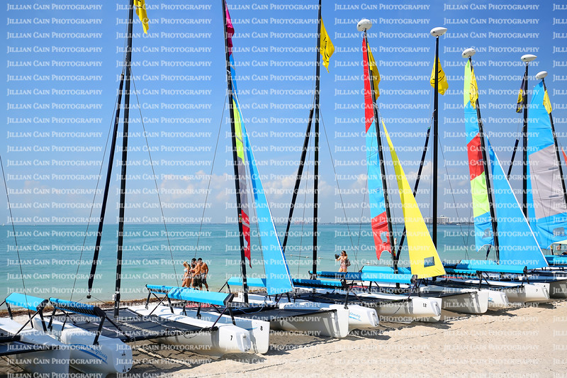 EDITORIAL USE ONLY:  Beautiful people walking by catamaran boats for rent on the shore at Rickenbacker Causeway.
