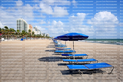 Blue lounge chairs and umbrellas line Fort Lauderdale Beach directly in front of the Atlantic Ocean.