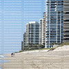 Beachgoers enjoy a morning walk between the surf and the condos on Singer Island, Florida, USA