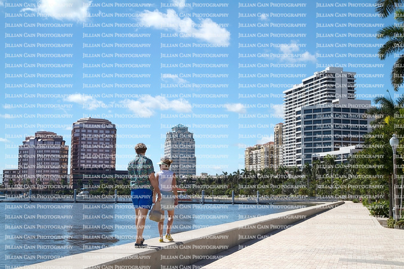 Couple walks on the seawall at the West Palm Beach waterfront on a beautiful fall day.