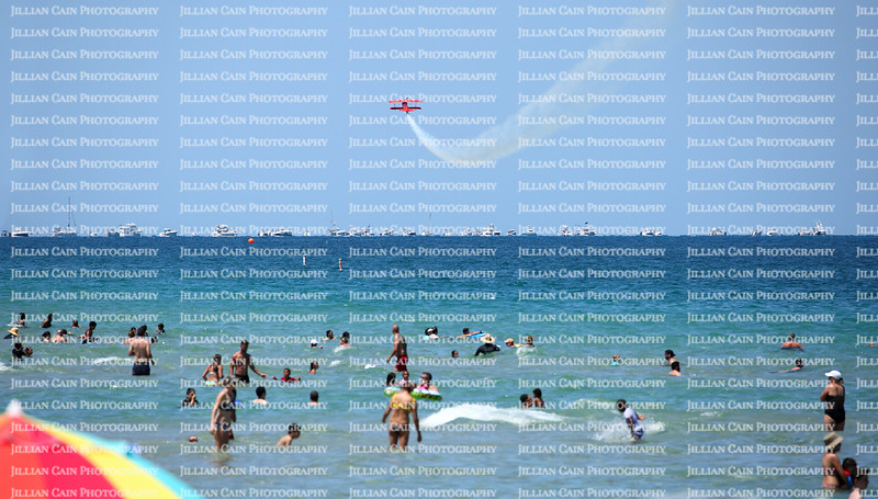 Fort Lauderdale beachgoers play in the Atlantic Ocean and watch the Fort Lauderdale Air Show planes perform their stunts.