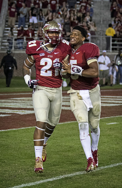 Defensive end Chris Casher celebrates his fumble recovery and 31 TD run with QB Jameis Winston.  Casher picked up the loose ball and ran 31 yards for an FSU TD after getting to Hunt in the backfield as the #2 ranked Florida State Seminoles dominated Syracuse 59-3 Saturday at Doak Campbell stadium.  The Seminoles complete the 2013 home stand next weekend against Idaho before travelling to Gainesville to close out the regular season.