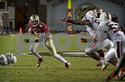 Jameis Winston escapes pressure and moves the chains with another first down.  Winston passed for 325 yards and a TD and rushed for 33 yards as the #3 Florida State Seminoles defeated the #7 ranked Miami Hurricanes 41-14 Saturday night in a top 10 ACC match-up of unbeaten teams.