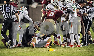 Penalty flags fly as Jameis Winston pushes teammate Bobby Hart away from Miami's Anthony Chikillo, who had just eye gouged Hart during a pile up. The Hurricanes were penalized on the play resulting in a first and goal for FSU.  The Seminoles scored on the ensuing play.  #3 Florida State Seminoles defeated the #7 ranked Miami Hurricanes 41-14 Saturday night in a top 10 ACC match-up of unbeaten teams.