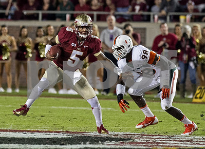 Jameis Winston eludes pressure from Miami's Jelani Hamilton.  Winston passed for 325 yards and a TD and also rushed for 33 yards as the #3 Florida State defeated the #7 ranked Miami Hurricanes 41-14 Saturday night in a top 10 ACC match-up of unbeaten teams.