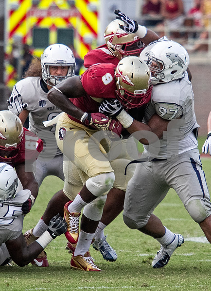 RB Karlos Williams runs through traffic in his debut at running back.  Williams led all rushers with 109 yards on the ground. Florida State defeated the Nevada Wolfpack 62-7.
