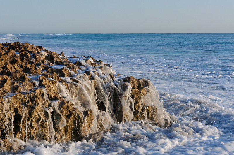 The waves slowing melt back into the sea.