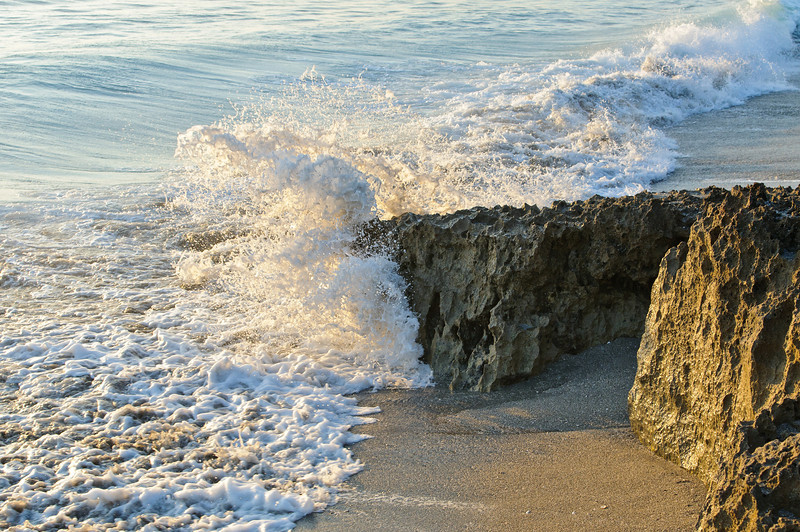 Back lit by the morning sun, waves glow as they break on the ancient limestone.