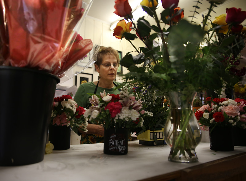 HOLLY PELCZYNSKI - BENNINGTON BANNER Lynn Frost, Owner of the Tuscan Sunflower buries herself around bouquets of flowers while arranging bouquets to prepare for Valentine's Day at her shop on North St. in Bennington on Monday afternoon.