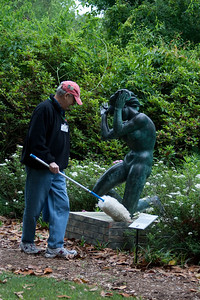 The statue seems to be recoiling  and the guy cleaning seems to have antlers growing out of his head! My, my!! So many things wrong with this picture.