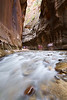 People crossing the Virgin river in the Narrows of Zion National Park.