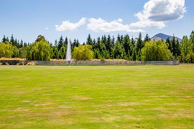 Flowers from Wanaka, Otago, New Zealand, Playing field, fountain, compound,  backdrop evergreens, mountain range,