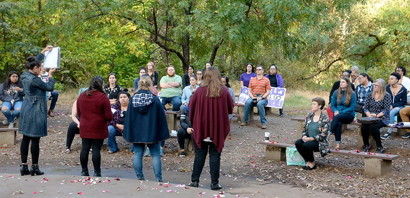 "Speakers share the stories of North State victims of domestic violence during the ""Flowers on the Creek"" Domestic violence victims remembrance at the One Mile Recreation Area of Bidwell Park in Chico, Calif. Thursday, Oct. 4, 2018.  The program, sponsored by Catalyst Domestic Violence Services, Chico Safe Place, Butte College Safe Place and Wellness Program, and the Butte County Child Abuse Prevention Council is in recognition of October as Domestic Violence Awareness Month. (Bill Husa -- Enterprise-Record)"