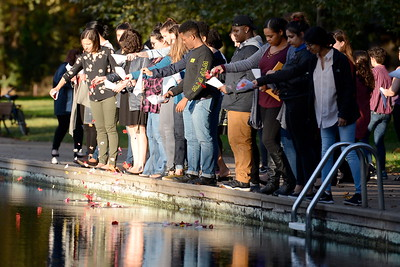 """About 40 people place flower petals in the creek during the """"Flowers on the Creek"""" Domestic violence victims remembrance at the One Mile Recreation Area of Bidwell Park in Chico, Calif. Thursday, Oct. 4, 2018.  The program, sponsored by Catalyst Domestic Violence Services, Chico Safe Place, Butte College Safe Place and Wellness Program, and the Butte County Child Abuse Prevention Council is in recognition of October as Domestic Violence Awareness Month. (Bill Husa -- Enterprise-Record)"""