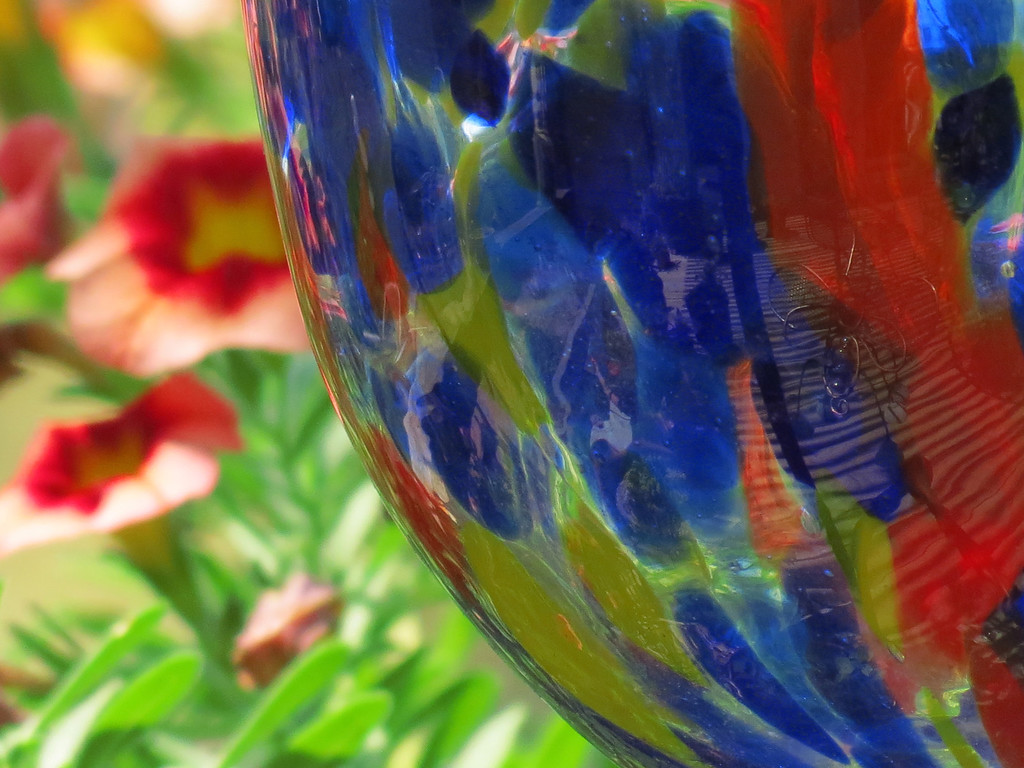 Colorful glass and Calibrachoa flowers.<br /> <br /> I have a plan. If it gets so hot and dry that we don't have flowers anymore this summer,<br /> I am going to replace all of the blooms with colorful glass ornaments -- <br /> maybe even some of Becky's glass and crystal that she has collected over the years; <br /> I'll just get them out of the curio cabinet when she is not looking, <br /> maybe she won't notice.