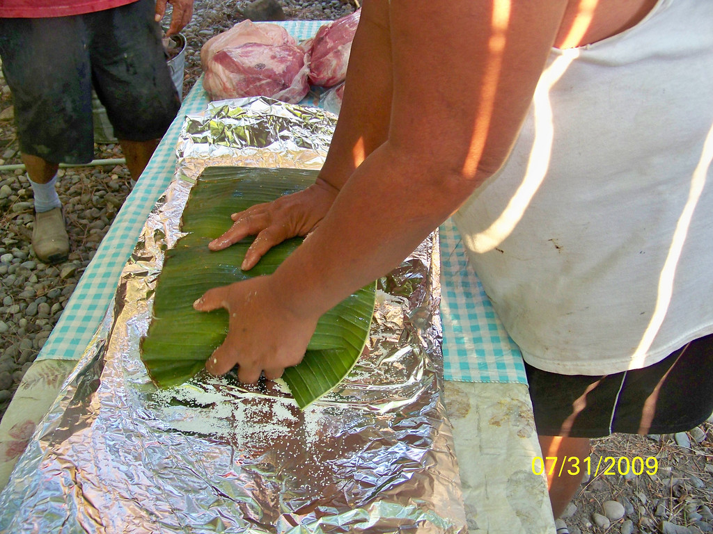Covering the wrapped pork with banana leaves.