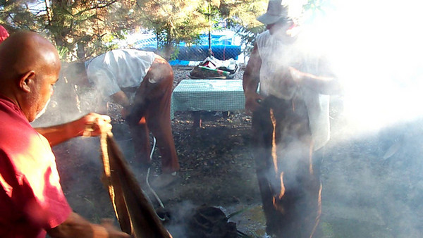 Spreading the wet burlap bags over the cattails/pork in the pit