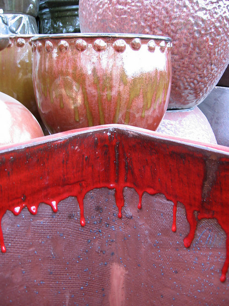 Colorful planters for sale.<br /> The square planter in the foreground has a bright red glaze dripping down the inside of it.