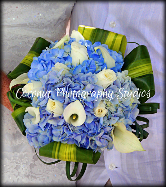 Bouquet 002<br /> Blue Hydrangeas with white roses and mini calla lilies, tropical leaves and lilys grass