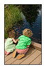 Two small children are entranced with the fish in a small pond at the Denver Botanical Garden.