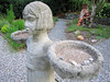 Sculpture of a girl with 'potted gardener' in bg
