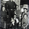 "Photo of the Floyd Bramwell family at the Red Ryder Ranch in 1953?  Taken by RR/Fred Harman.  Seated: Virginia, standing Floyd and Gary, kneeling left to right""  Marvel (doll from Gram Bramwell), Doug and Connie behind.  Mom was 38, Dad 40, Connie 12, Doug 9, Gary 8, and Marvel 6.  We don't have a clue why the boys have dolls! because they never played with them!."