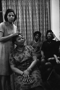 Charm school director showing students how to pluck their eyebrows. Harlem, New York.