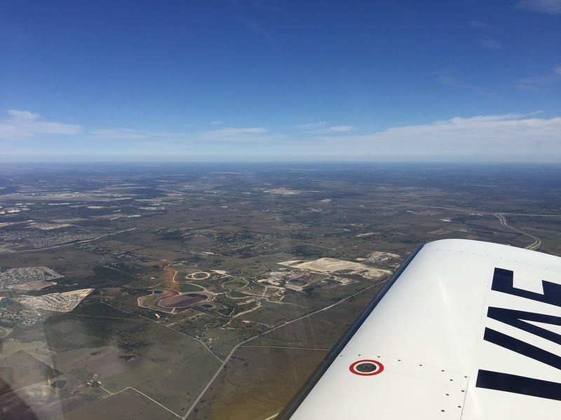 Circuit of the Americas (F1 track) SE of Austin on the way back (centered near horizon).